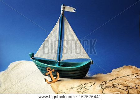 Wooden boat and old map on blue background. Columbus Day concept