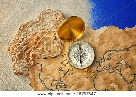 Compass, net and old map on blue background. Columbus Day concept