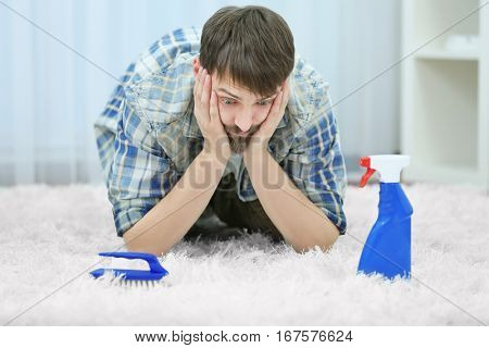 Desperate young man cleaning carpet at home