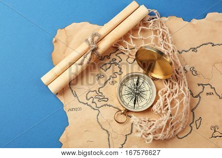 Compass, scroll and old map on blue background. Columbus Day concept