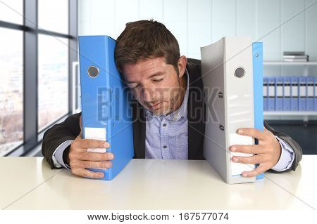 young attractive busy businessman overwhelmed suffering crazy stress at office exhausted and helpless holding paperwork folders napping on desk in business frustration and overwork problem poster