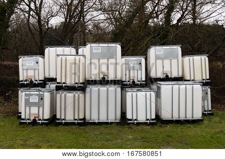 Bath UK - January 29 2017: Stack of intermediate bulk containers outdoors. Multiple IBC plastic chemical containers sitting empty with supplier labels visible