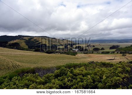 Broad panorama of the countryside in Victoria with green field in foreground. Grassy hills near Glenaire in Australia. Rural landscape near the forest in mountains. Hillside landscape.