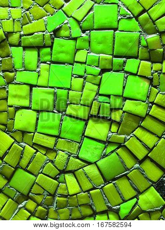 Green mosaic tiles of irregular sizes arranged in a background motif. Space for text.
