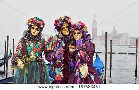 VENICE, ITALY - FEBRAURY 2: Carnival of Venice three beautiful masks with venetian lagoon FEBRUARY 2, 2016 in Venice, Italy