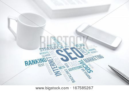 Seo search engine optimization business concept word cloud. Print document smartphone book pen and coffee cup. Blue toned.