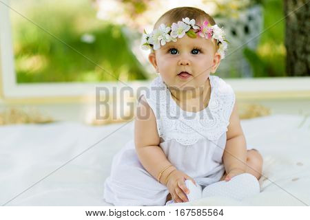 Baby girl outdoors portrait. Sunny Green Summer background. Portrait of beautiful angel girl playing outside wearing a white dress and flowers wreath