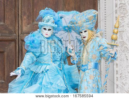 VENICE, ITALY - FEBRAURY 2: Carnival of Venice two beautiful masks with scepter and umbrella FEBRUARY 2, 2016 in Venice, Italy