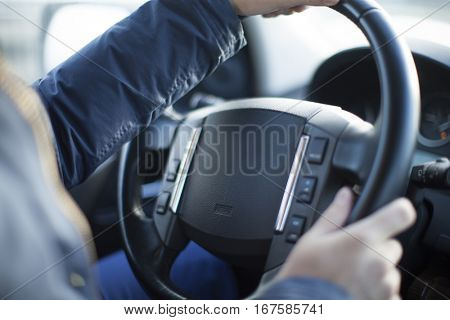 A hand pushes the cruise control button on a steering wheel.