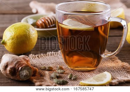 Hot tea with lemon ginger and cardamom over rustic wooden background close up