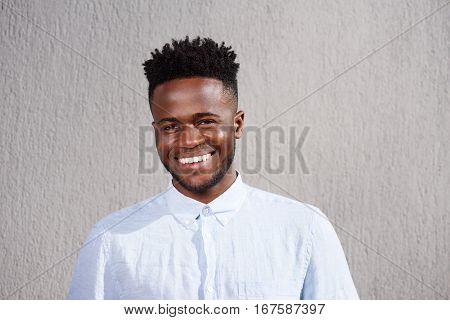 Attractive African Man Smiling And Standing By Wall