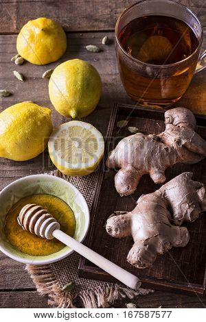 Ginger lemon and honey as ingredients for healing tea over rustic wooden background