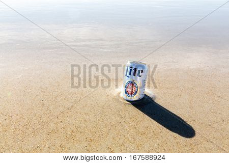 Old Orchard Beach, USA - 3rd Sept 2014: Illustrative editorial image of a can of Miller Lite beer being kept cold in the sea. A popular pale light beer produced by Millercoors since 1973