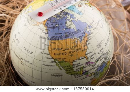 Thermometer Placed On A Little Model Globe