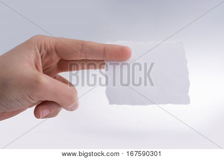 Hand Holding A Piece Of Torn Paper