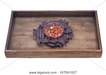 Pico de gallo, authentic mexican salsa in bpa free plastic container and lightly salted organic blue corn tortilla chips on wooden vintage tray