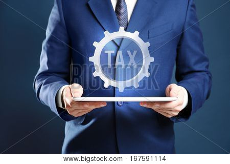 Man holding tablet and gear wheel with word TAX. Taxation concept