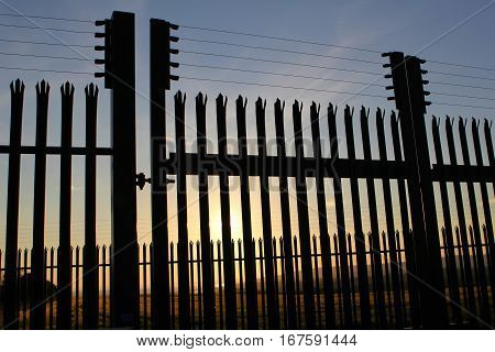 High security steel and razor wire fence with unreachable sunset landscape behind it