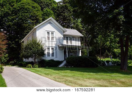 A white home below the bluff on Fourth Street in Harbor Springs, Michigan, during August.