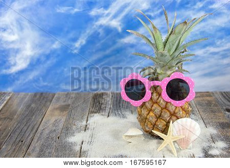 pineapple with pink sunglasses in sand with starfish and seashells on rustic wood