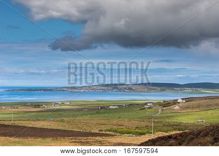 Orkneys Scotland - June 5 2012: Look west to the town of Stromness across arm of Atlantic Ocean under blue cloudy sky. Brown fields and green meadows in front. Blue ocean dark green hills on horizon.