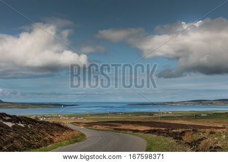 Orkneys Scotland - June 5 2012: Landscape looking at entrance to blue Atlantic Ocean under blue cloudy sky. Foreground is meandering road between brown fields green meadows and farms. Main Island.