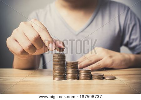 Man hands putting coins stack Concept business finance save money and investment