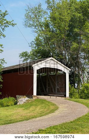 The Neet Covered Bridge crosses Little Raccoon Creek on County Road South 80 East in Parke County Indiana USA. This single span Burr Arch Truss structure has a length of 126 feet or 144 feet including the 9-foot overhang at each end. Built in 1904 by Jose