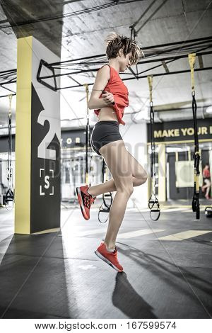 Beautiful girl jumps with a skipping rope in the gym on the background of the hanging TRX straps. She wears black shorts, red sleeveless and sneakers. Her hair is flying in the air. Vertical.