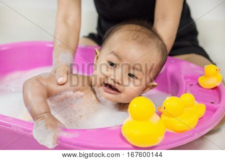 Baby Taking A Bath In Bathtub And Playing With Foam Bubbles