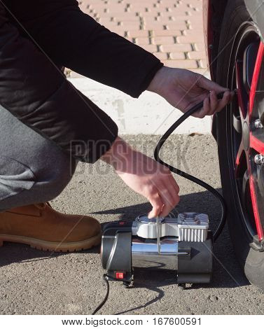 Man checking air pressure and filling air in the tires of car with air compressor.