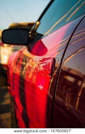 Shining handle of red car door with blurred background