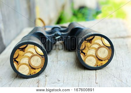 black binoculars. Big telescope on wooden background. Money.