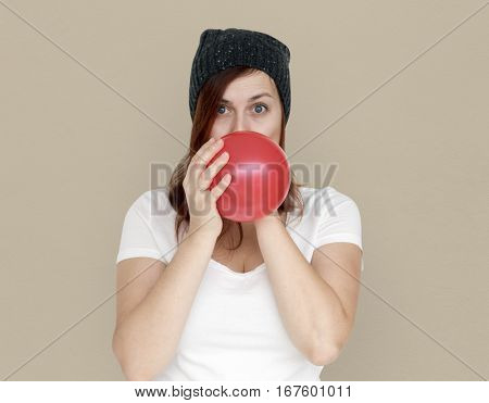 Woman Blowing Balloon Playful Studio Portrait