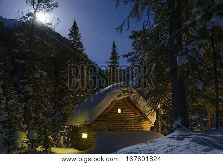 Winter moonlit night, snow and the light from windows of a wooden hut. Full moon on the hill.