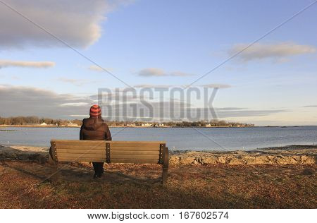 woman on park bench looking out to the ocean at sunset