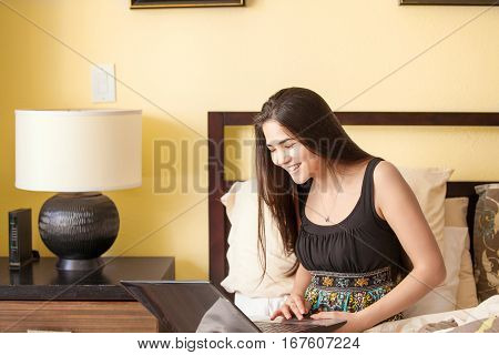 Beautiful biracial Caucasian Asian teen girl sitting on bed looking at laptop smiling in room with yellow walls