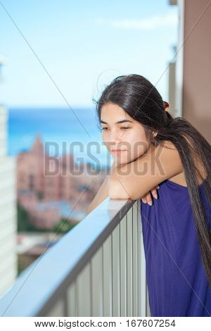 Biracial teen girl standing on outdoor highrise patio sad and thinking urban ocean background