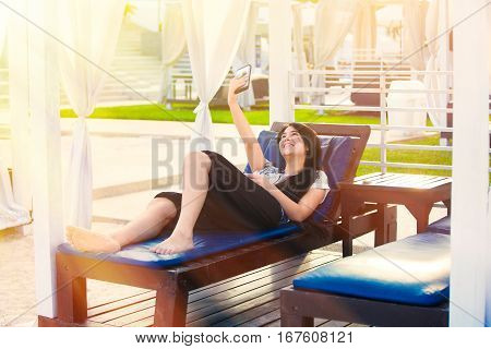 Beautiful biracial teen girl sitting under sun shade with white curtains at resort taking selfie using smartphone