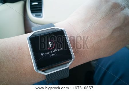 Perspective view of person reading wrist watch with heart and steps tracker while driving poster