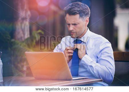 Handsome businessman adjusting tie while using laptop at sidewalk cafe