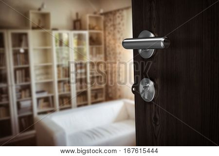 Closeup of brown door with key against sofas by cabinets at home