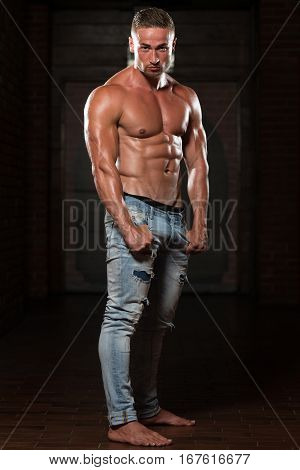 Young Man In Jeans Flexing Muscles