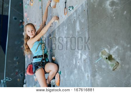 One Teenager Climbing A Rock Wall Indoor.