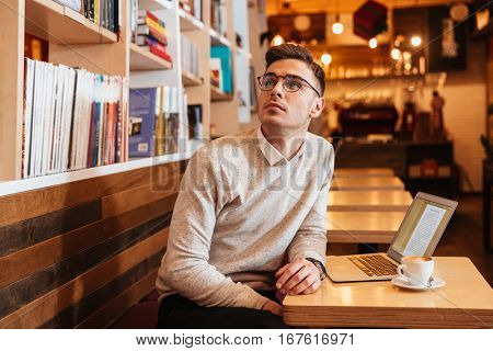 Photo of attractive young man sitting in cafe and using laptop while drinking coffee and look aside.