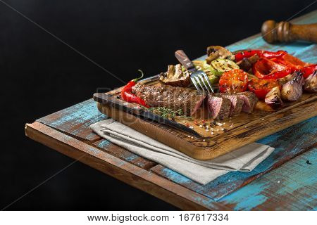 Sliced steak grill with grilled vegetables on the wooden table with a fork and a knife