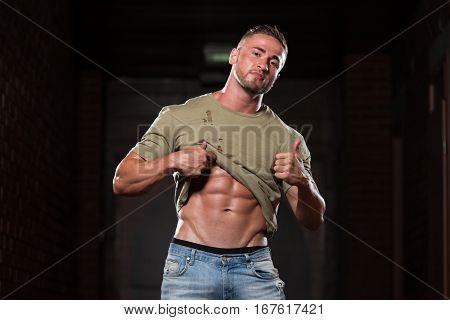 Muscular Bodybuilder In Jeans Flexing Muscles