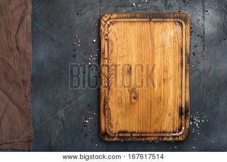 Blank cutting board with cloth napkin on a stone dark surface top view