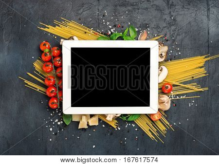 White tablet with copy space and ingredients for cooking Italian pasta on dark stone surface top view