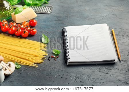 Notebook with blank pages and ingredients for cooking Italian pasta on dark stone surface